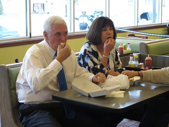 Republican vice presidential nominee Mike Pence, sitting next to his wife Karen, eats a hot dog with chili sauce from the Jib Jab Hot Dog Shoppe during a campaign stop in Girard, Ohio, Wednesday, Sept. 28, 2016.