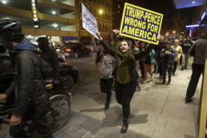 Demonstrators march following a protest against President-elect Donald Trump in downtown Indianapolis on Saturday, Nov. 12, 2016. Tens of thousands of people marched in streets across the United States on Saturday, staging the fourth day of protests of Trump's surprise victory as president. (AP Photo/AJ Mast)